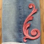 large pink scroll on jean legs