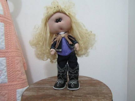 doll dressed in cowboy clothes and boots